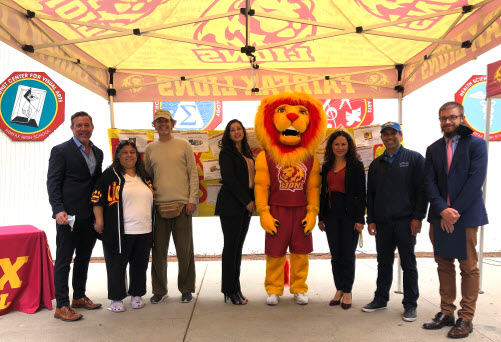 People posing for picture with lion mascot